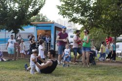 A man dances with his daughter as an audience gathers to watch the TACO team perform music in a local park.
