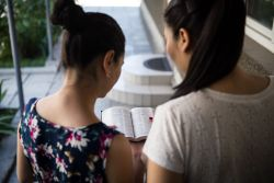 Two Central Asians read the Bible together.