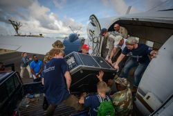 OM workers help Samaritans Purse workers unload a reverse osmosis, desalination machine off a Missions Aviation Fellowship plane on the island of Barbuda in the Caribbean. Photo by Garrett N.