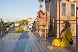 A worker in Central Asia talks to a homeless woman begging on a pedestrian overpass.