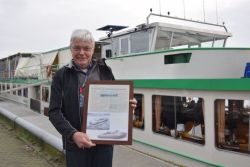 OM Riverboat Captain, Klaas Kattouw, showing the newspaper article of the ship from the olden days.