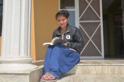 A local believer enjoys time outside reading a book.