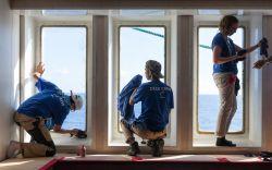 At Sea :: Crewmembers grease the windows of Logos Hope.