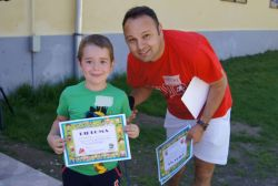 A child receiving his diploma for participating in the Kids Games program
