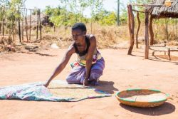 A woman spreads out rice to dry outside of her home in northern Mozambique.