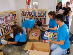 Coatzacoalcos, Mexico :: Crewmembers set up a library in a village, as local people look on.