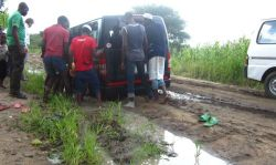 People discuss the best way to get a vehicle out of mud.