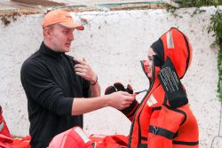 Chile: Valparaiso, Chile :: As part of a week of pre-ship safety training, Aksel-Johan Anderson (Norway) helps train new crewmembers how to use immersion suits. More Info
