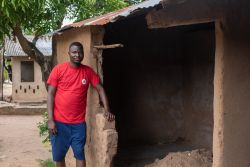OMer Estavao stands outside of his home in Mozambique. The back wall collapsed during the rains of Cyclone Idai. Photo by Rebecca Rempel